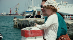 Little funny kid and young mother are studies equipment for fishing. - stock footage