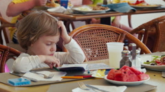 Little child seating at the restaurant, eats watermelon, drawing something. Stock Footage