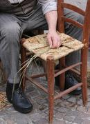 senior mender of chairs while with straw shelters the old wooden kitchen Chai - stock photo