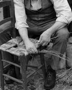 old man mender of chairs while repairing old chair - stock photo