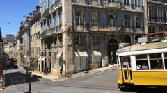 A yellow tram passing by a crossroad in downtown Lisbon Stock Footage
