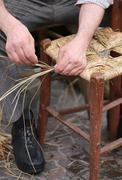 old mender of chairs while repairing old wooden chair - stock photo
