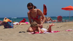 Nice pretty mom doing massage to her little doughter on the beach. - stock footage