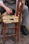 hands of a mender of chairs while repairing an old chair - stock photo