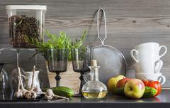 Kitchen work surface with crockery, kitchen utensils and ingredients, still life - stock photo