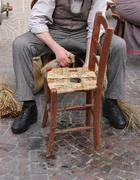 Senior artisan mender of chairs with woven straw shelters an old wooden chair Stock Photos
