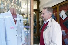 Mature man looking at suit jacket in tailors shop window Stock Photos