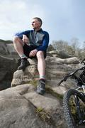 Mature male mountain sitting and looking out from rock formation - stock photo