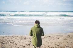 Rear view of man looking out to sea from windy beach, Sorso, Sassari, Sardinia, Stock Photos