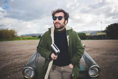 Mid adult man leaning against vintage car with vintage movie camera - stock photo