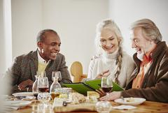 Senior friends looking at book at dinner - stock photo