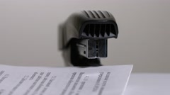 Close up of stapler, stapling sheets of paper  Stock Footage