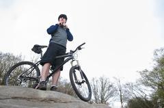 Mature male mountain biker fastening helmet on rock formation Stock Photos