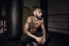 Tattooed male boxer crouching next to punch bag in gym Stock Photos