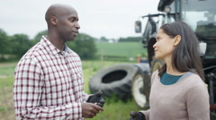 4K Portrait of smiling farming couple standing next to tractor  Stock Footage