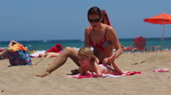 Nice pretty mom doing massage to her little doughter on the beach. Stock Footage