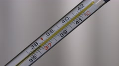 Glass mercurial thermometer takes temperature on white background Stock Footage