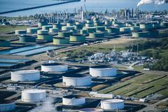 High angle view of oil storage tanks in coastal oil refinery - stock photo