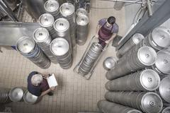 Brewers moving kegs in brewery - stock photo