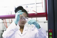 Female scientist using pipette and volumetric flask in lab - stock photo