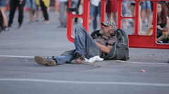 on the sidelines of the roadway homeless man lying on the bag - stock footage