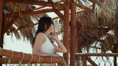 Beutiful tunning woman stands under the tropical roof and talking by phone. Stock Footage