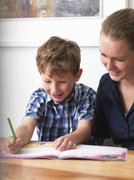 A six year old being helped with his homework by his mother at home Stock Photos