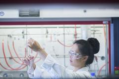 Young female scientist  pipetting sample into volumetric flask in lab - stock photo