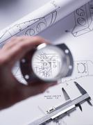 Engineer holding a precision made component over a technical drawing with a dial Stock Photos