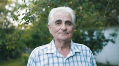 Portrait of senior man with gray hair in the garden Stock Footage