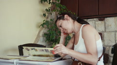 Beautiful woman sitting and reading menu in the Greek cafe. Arkistovideo