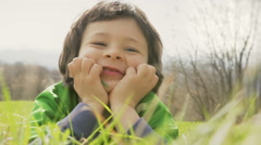 Happy child close up make faces lay down on grass in sunny day Stock Footage