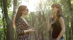 Girls talking and smoking the e-cigarette in the park Stock Footage