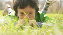 Happy child close up lay down on grass in sunny day Stock Footage