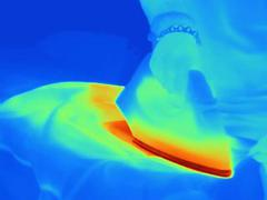 Thermal image of womans hand ironing at home - stock photo