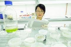 Female scientist using digital tablet in plant sample lab - stock photo