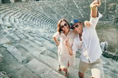 Funny couple take a selfie photo in antique amphitheatre in Side, Turkey Stock Photos