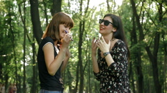 Girl vividly tells the story her friend who smokes an e-cigarette in the park Stock Footage