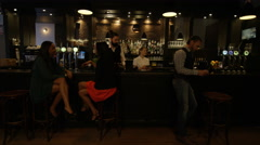 4K Young diverse group socializing & bartender serving drinks in trendy city bar - stock footage