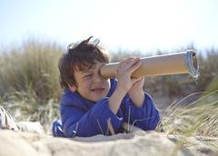 Young boy on beach, looking through pretend telescope Stock Photos