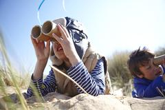 Two young boys on beach, looking through pretend binoculars - stock photo
