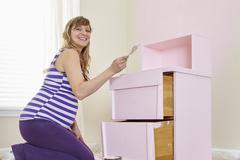 Portrait of pregnant woman painting nursery dresser pink - stock photo