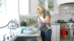 Busy Mother With Baby In Sling At Home Stock Footage