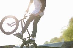 Young man doing stunt on bmx at skatepark - stock photo
