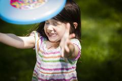 Young girl throwing frisbee in garden - stock photo