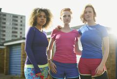 Portrait of three women standing together wearing sports clothing - stock photo
