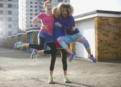 Portrait of three women wearing sports clothing jumping - stock photo
