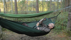 A man in a hammock making video on selfie stick with action camera. Man in the Stock Footage