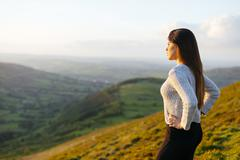 Rear view of young woman looking out over Glyn Collwn valley, Brecon Beacons, - stock photo