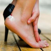 Injured foot because of high heels, little white patch on ankle. Hand making - stock photo